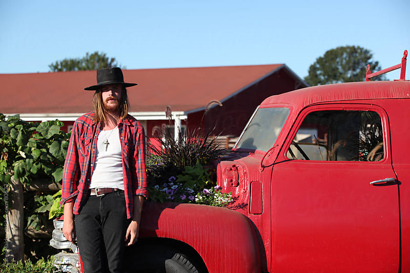 A Cowboy In Front Of A Antique Truck by Carey Haider for Stocksy United