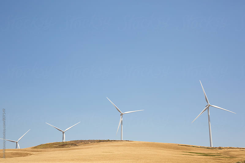 Wind turbines set against a sunny blue sky by Jon Attaway for Stocksy United