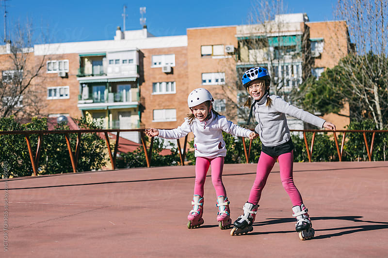 Two Sisters Roller Skating in an Outdoor Rink by Victor Torres for Stocksy United