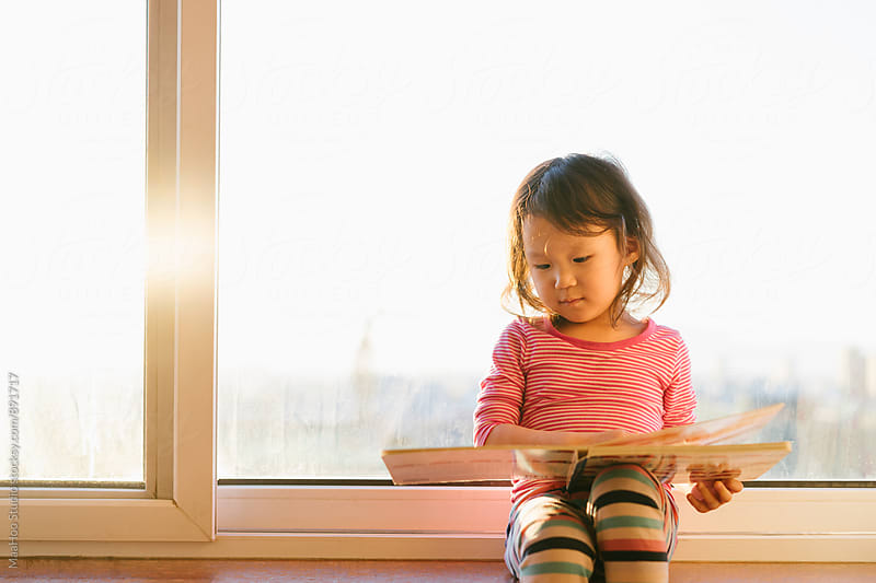 Toddler girl reading on balcony by MaaHoo Studio for Stocksy United