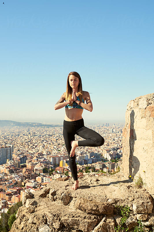 Fit woman in tree pose with hands in namaste by Guille Faingold for Stocksy United