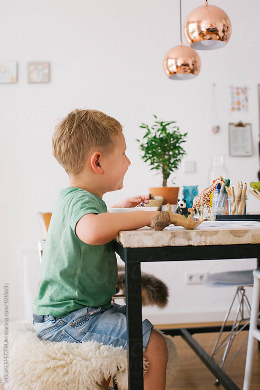 Profile of Small Blond Boy Sitting on Kitchen Table With Animal Toys by Julien L. Balmer for Stocksy United