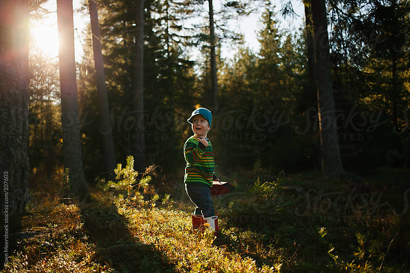 Cute little boy with red boots standing in the forest. by Koen Meershoek for Stocksy United