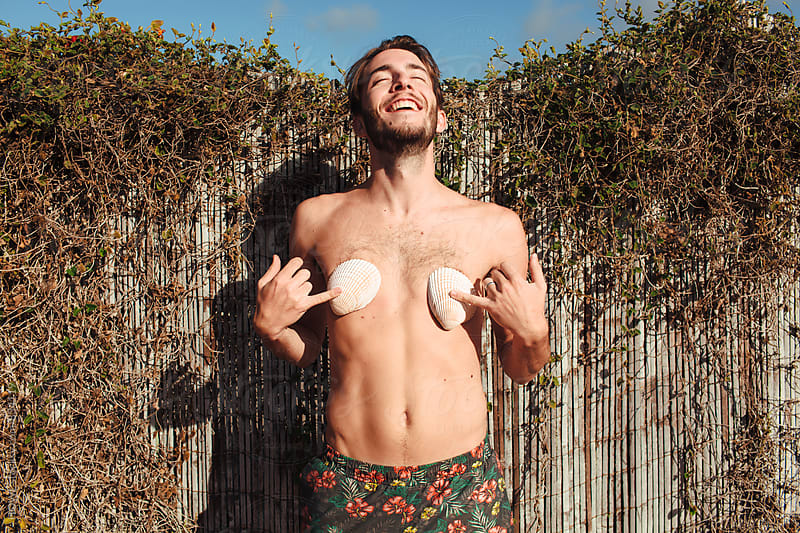 a goofy young man poses with sea shells in an inappropriate manner  by HOWL for Stocksy United