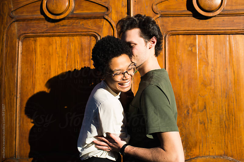 Young man kissing his smiling girlfriend outdoors by michela ravasio for Stocksy United