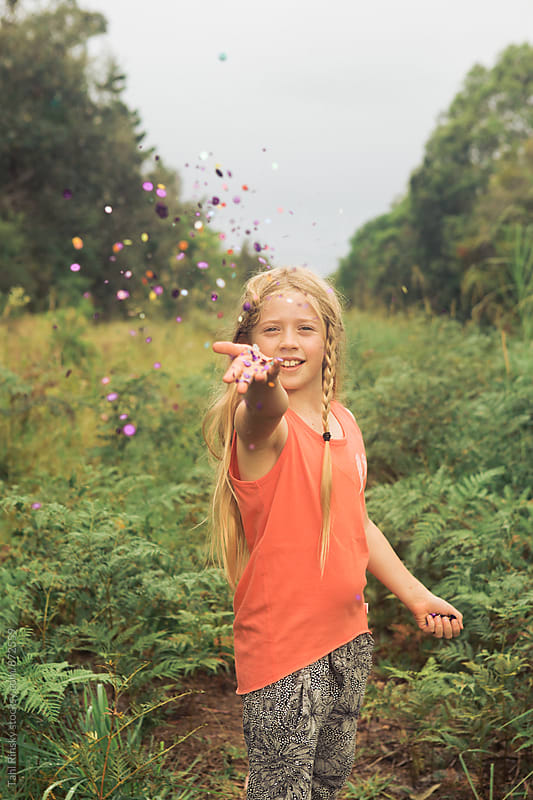 girl outdoors throwing confetti into camera  by Tahl Rinsky for Stocksy United