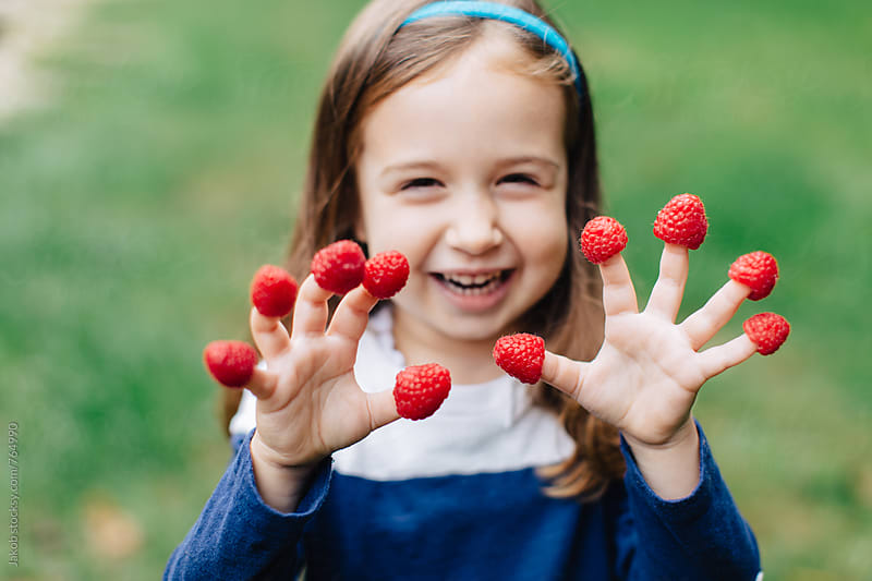 Cute young girl with raspberries on her fingers by Jakob for Stocksy United