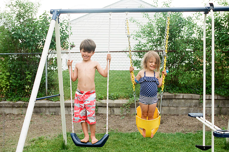 children on backyard swingset by Maria Manco for Stocksy United