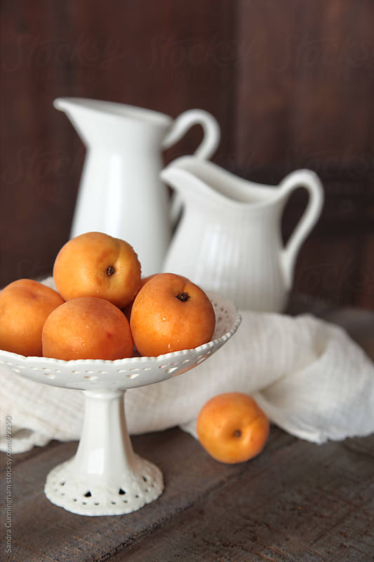 Fresh peaches in bowl on old brown table by Sandra Cunningham for Stocksy United