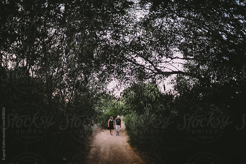 Old couple walking on the path under the tree by Evgenij Yulkin for Stocksy United