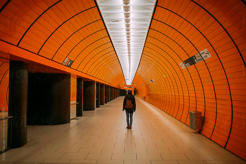 Woman standing in underground subway station by Maja Topcagic for Stocksy United