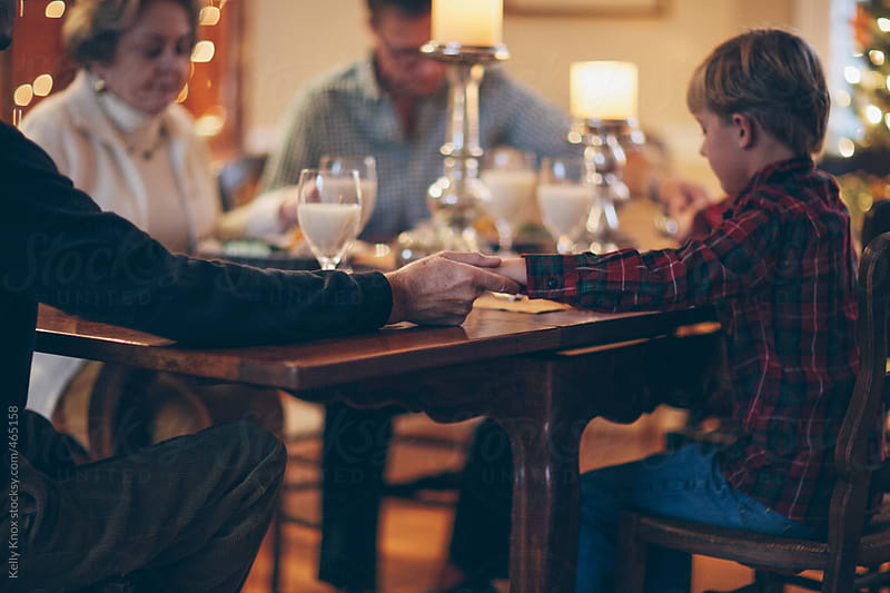 multi-generational family at the dining table for a holiday meal by Kelly Knox for Stocksy United
