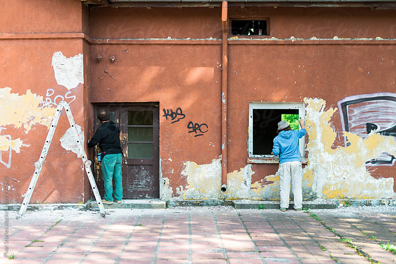 Two graffiti artists preparing wall for painting by Pixel Stories for Stocksy United