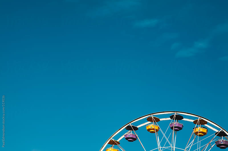 Ferris wheel at amusement park, blue sky in background by Paul Edmondson for Stocksy United