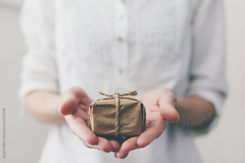 A woman holds a little gift in her hands by Jacqui Miller for Stocksy United