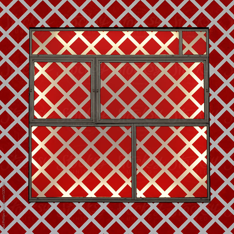 Red diagonal square patterned front of a commercial building. Interior illuminated by sunlight by Paul Phillips for Stocksy United