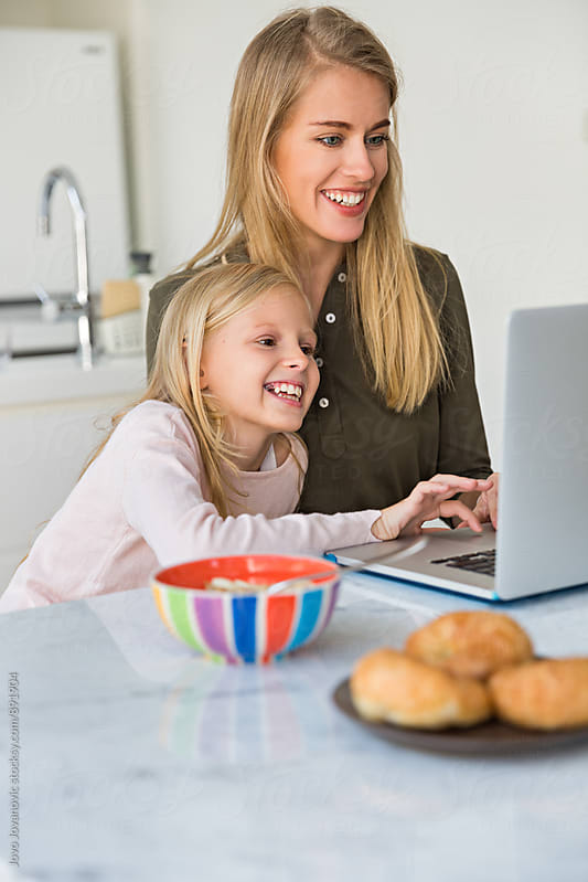 Mother teaching her daughter how to use computer by Jovo Jovanovic for Stocksy United