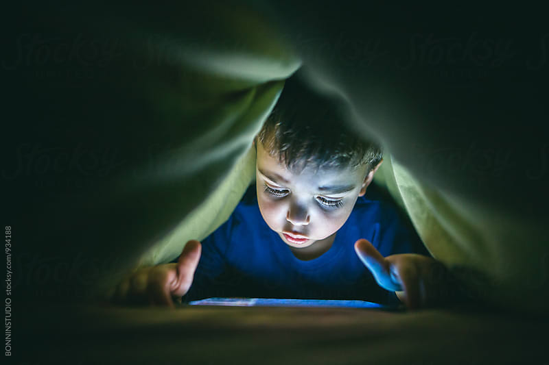 Little boy watching a video under the bed sheets. by BONNINSTUDIO for Stocksy United