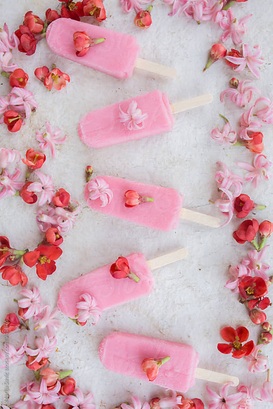 Pink popsicles in row surrounded by flower buds by Marija Savic for Stocksy United