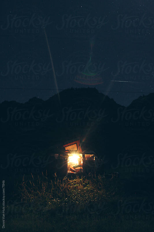 Camper, camping under the stars in the darkness by Denni Van Huis for Stocksy United