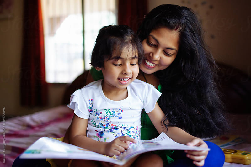 Little girl reading a book sitting on her mother's lap by Saptak Ganguly for Stocksy United