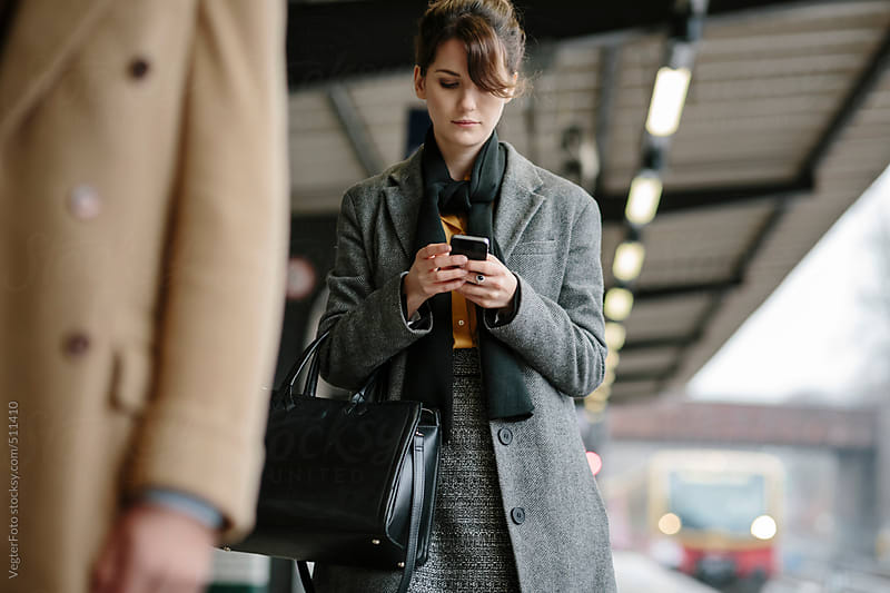 Businesswoman At Train Station Checking News On Smart Phone by VegterFoto for Stocksy United