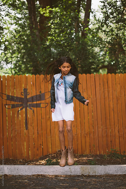 Young Girl Jumping in front of Fence by Gabrielle Lutze for Stocksy United