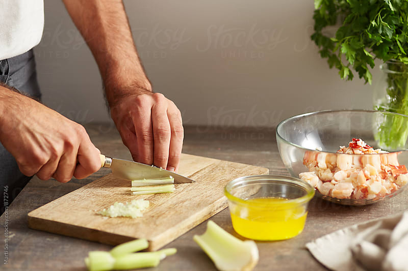 Man cutting celery for lobster roll by Martí Sans for Stocksy United