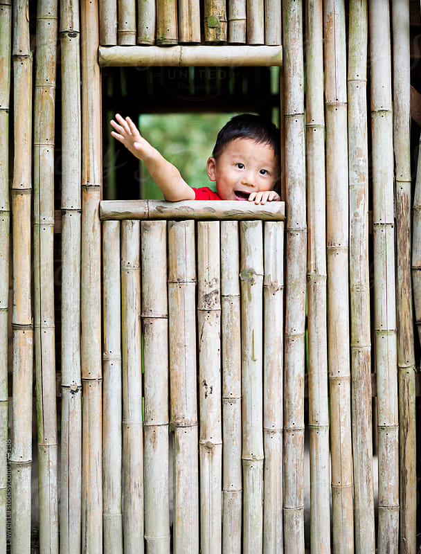 Child playing happily in tree house by Lawren Lu for Stocksy United