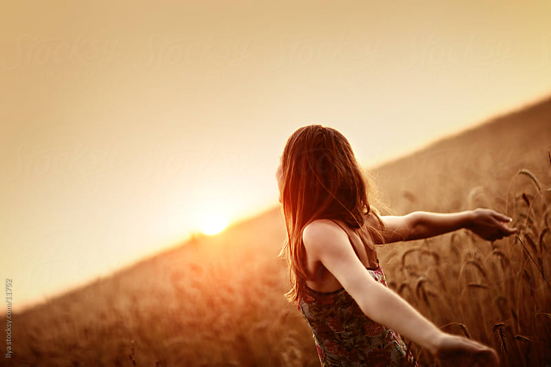 Young woman with raised arms in the field on sunset. by Ilya for Stocksy United