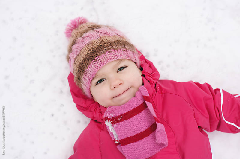 Little girl enjoying her time spent in the snow lying on the ground. by Lea Csontos for Stocksy United