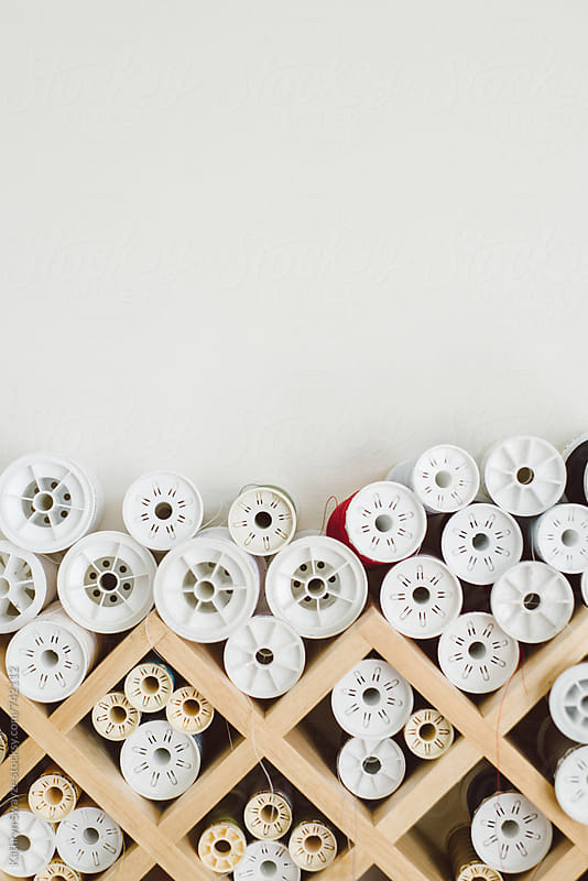 Spools of thread stacked on a grid-based organizer by Kathryn Swayze for Stocksy United