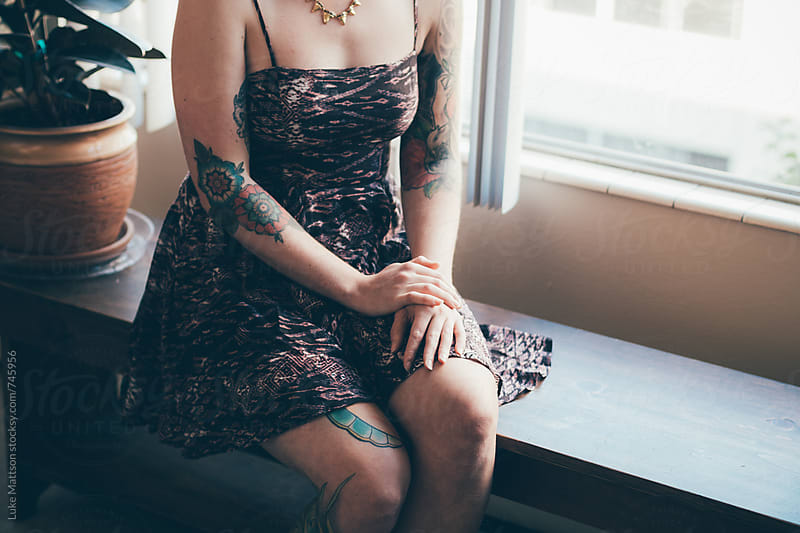 Young Tattooed Woman Wearing Dress Sitting On Bench By Window by Luke Mattson for Stocksy United