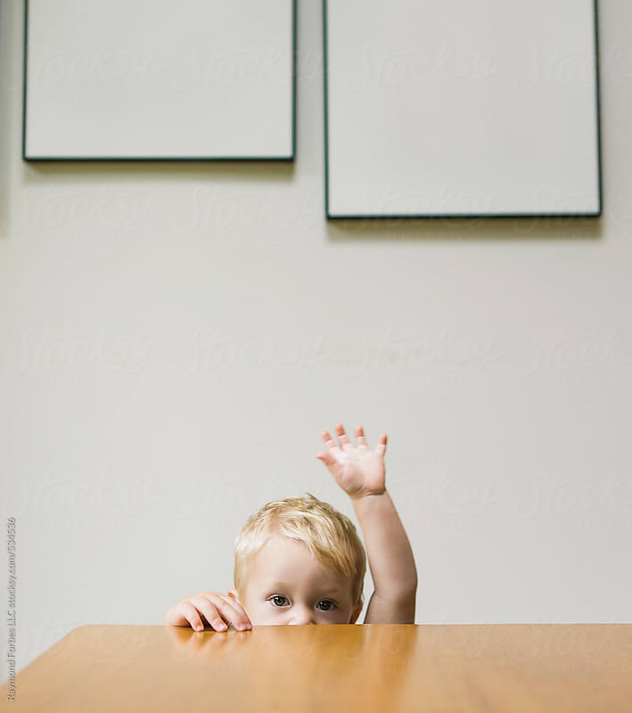 Shy boy behind the table raising his hand by Raymond Forbes LLC for Stocksy United