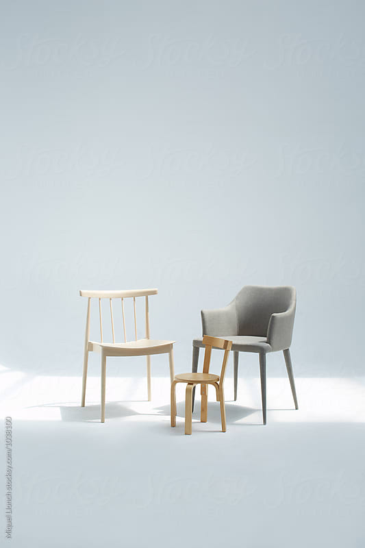 Two big chairs and one small gathered as a family by Miquel Llonch for Stocksy United