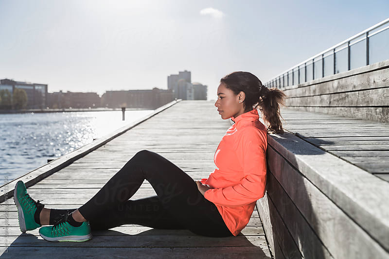 Mixed race female athlete resting outdoors after workout by Lior + Lone for Stocksy United