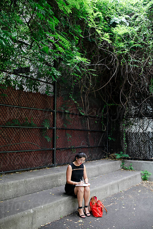 Woman sitting on steps in urban park, writing in notebook by Jennifer Brister for Stocksy United