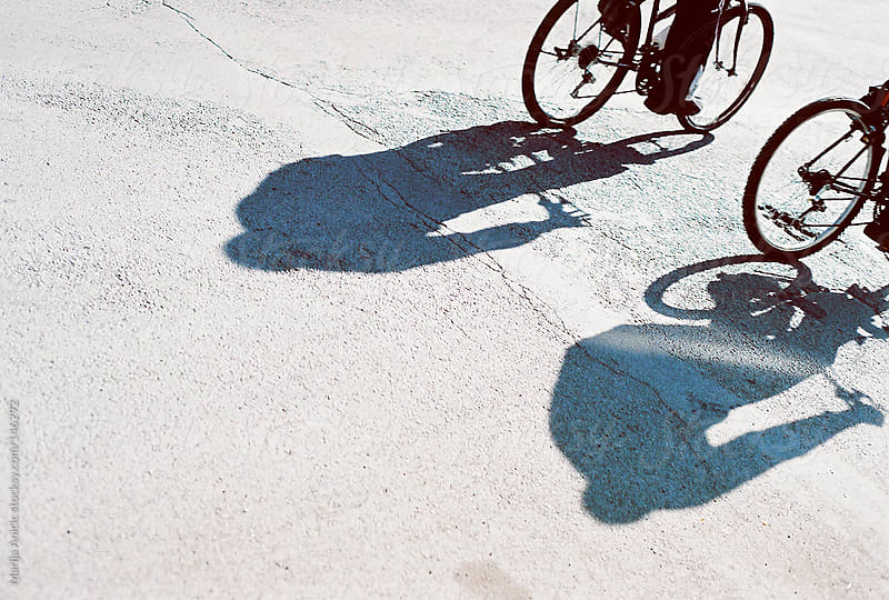 Shadows of two bicyclists  by Marija Anicic for Stocksy United