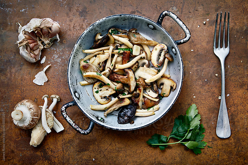 Cooked mushrooms with garlic and parsley by James Ross for Stocksy United