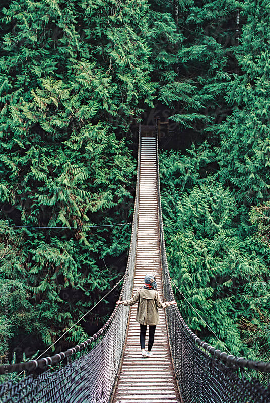 Woman crossing bridge in forest by Daniel Kim Photography for Stocksy United