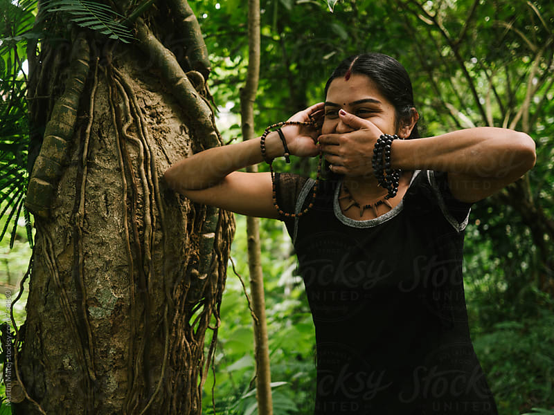Indian girl trying to stop laughing in the jungle by Martin Matej for Stocksy United