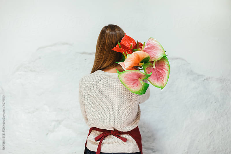 Back view of a woman holding a bouquet of flowers. by BONNINSTUDIO for Stocksy United
