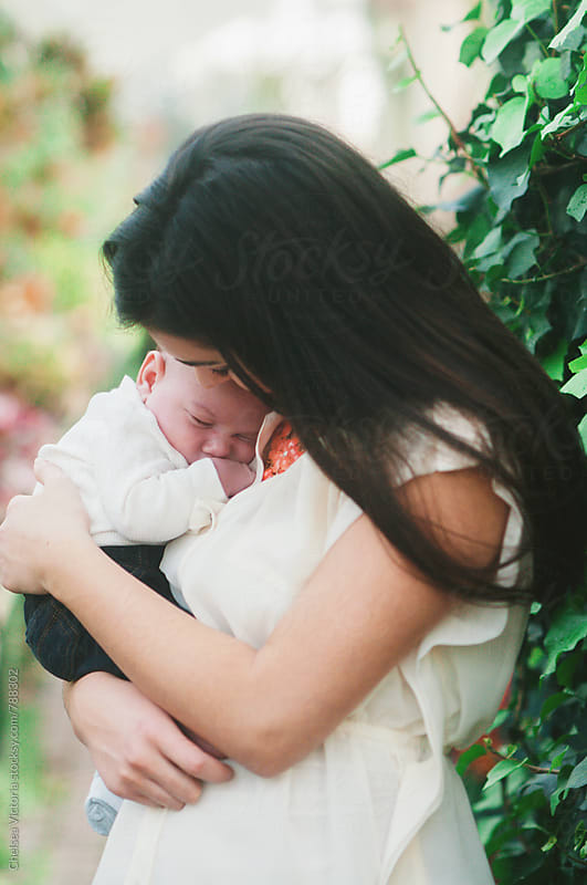 A mother holding her newborn baby by Chelsea Victoria for Stocksy United