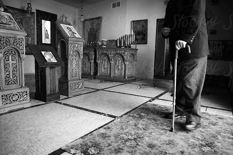 Lower portion of old man walking with cane at Greek church by Dina Giangregorio for Stocksy United