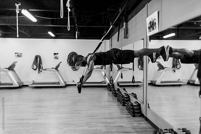 Fit and muscular african american using suspension bands during workout by Jakob for Stocksy United