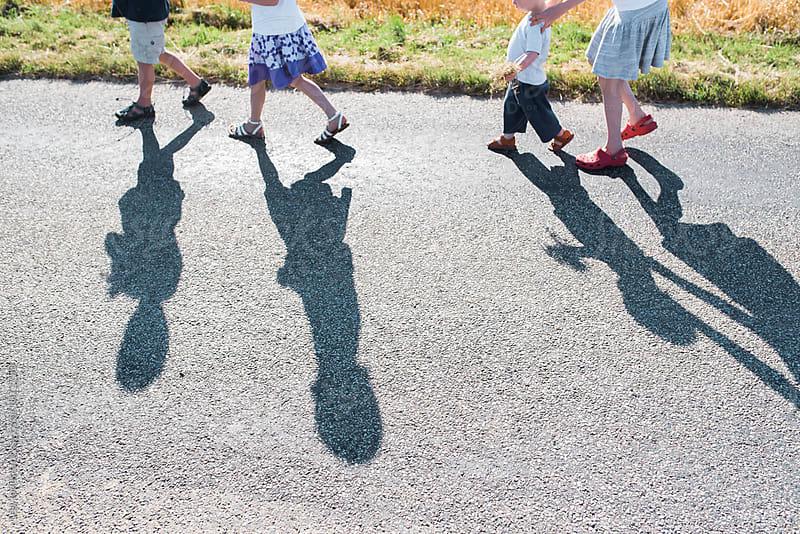 four kids walking on a road by Léa Jones for Stocksy United