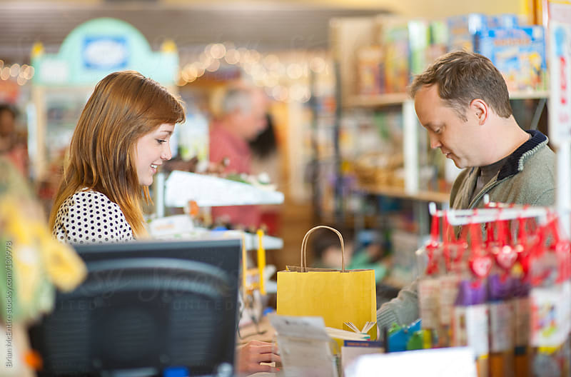 Cashier Woman in Toy Store Completing Purchase Transation by Brian McEntire for Stocksy United
