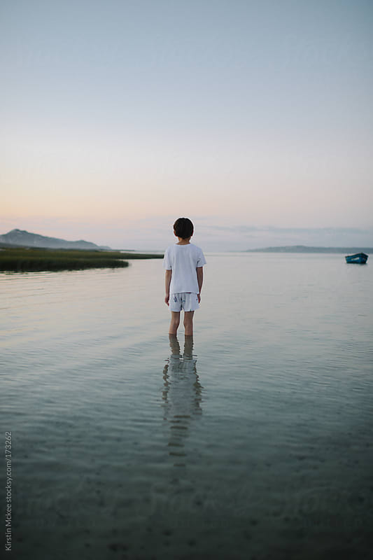 Boy standing in a lagoon at sunset by Kirstin Mckee for Stocksy United