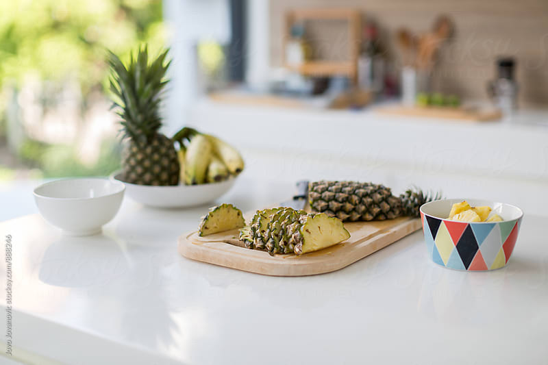 Snack time - sliced pineapples on kitchen counter by Jovo Jovanovic for Stocksy United