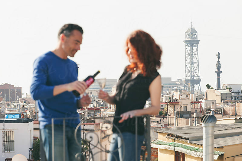Defocused beautiful couple drinking wine on the rooftop. by BONNINSTUDIO for Stocksy United